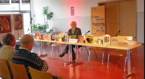 """Ion Lazu, înconjurat de cărţile lui şi ale soţiei lui, Lidia Lazu, ţinînd conferinţa """"Situaţia dramatică a scriitorului din România în timpul comunismului,"""" decembrie 2013."""