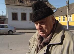 Mihai Eisikovits la pas prin Gherla. In fundal cladirea scolii evreiesti de odinioara.